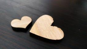 Δύο ξύλινες καρδιές που τοποθετούνται ωραία σε ένα τυρκουάζ εκλεκτής ποιότητας ξύλινο υπόβαθρο Στοκ Φωτογραφίες