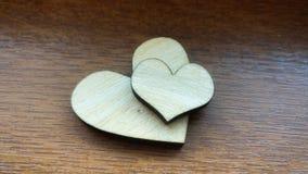 Δύο ξύλινες καρδιές που τοποθετούνται ωραία σε ένα τυρκουάζ εκλεκτής ποιότητας ξύλινο υπόβαθρο Στοκ Εικόνες