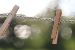 Δύο ξύλινοι γόμφοι ενδυμάτων clothespins στη σκοινί για άπλωμα Στοκ Εικόνες