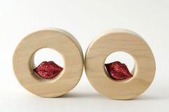 Δύο ξύλινοι κύκλοι με τα μικρά κόκκινα shinny χείλια στοκ φωτογραφίες με δικαίωμα ελεύθερης χρήσης