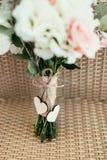 Δύο ξύλινες καρδιές με το τόξο στη γαμήλια ανθοδέσμη στοκ φωτογραφία