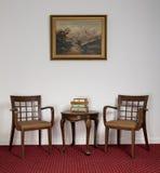 Δύο ξύλινες πολυθρόνες, μικρό στρογγυλό τραπεζάκι σαλονιού και πλαισιωμένη ζωγραφική Στοκ εικόνα με δικαίωμα ελεύθερης χρήσης