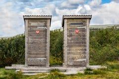 Δύο ξύλινες outhouse τουαλέτες με την κόκκινη καρδιά στο τοπίο βουνών Στοκ φωτογραφία με δικαίωμα ελεύθερης χρήσης