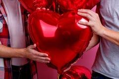 Δύο ομοφυλοφιλικοί τύποι κρατούν έναν σωρό των σφαιρών ηλίου με μορφή μιας καρδιάς Ρόδινη ανασκόπηση στοκ φωτογραφία με δικαίωμα ελεύθερης χρήσης