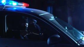 Δύο οπλισμένοι κακοποιοί που οδηγούν το περιπολικό της Αστυνομίας στην κακή γειτονιά, που στοχεύει τα πυροβόλα όπλα στο θύμα φιλμ μικρού μήκους