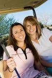 Δύο παίκτες γκολφ γυναικών που κάθονται στο κάρρο γκολφ Στοκ Εικόνες