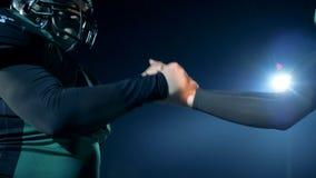 Δύο παίκτες τινάζουν τα χέρια και τα κεφάλια προσκρούσεων στα κράνη πριν από ένα παιχνίδι σε έναν τομέα 4K απόθεμα βίντεο
