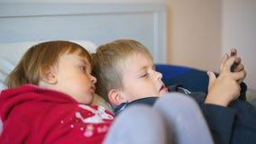 Δύο παιδάκια που προσέχουν το βίντεο στο smartphone Στοκ Εικόνες