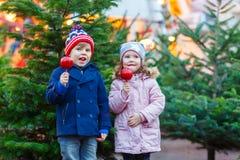 Δύο παιδάκια που τρώνε το μήλο ζάχαρης στην αγορά Χριστουγέννων Στοκ φωτογραφία με δικαίωμα ελεύθερης χρήσης