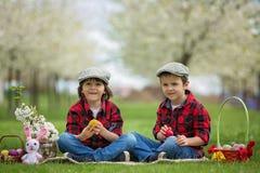 Δύο παιδιά, αδελφοί αγοριών, που έχουν τη διασκέδαση με τα αυγά Πάσχας στο π Στοκ Εικόνες