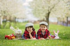 Δύο παιδιά, αδελφοί αγοριών, που έχουν τη διασκέδαση με τα αυγά Πάσχας στο π Στοκ εικόνα με δικαίωμα ελεύθερης χρήσης