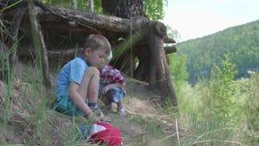 Δύο παιδιά παίζουν κοντά σε ένα μεγάλο δέντρο Οι ρίζες ενός κωνοφόρου δέντρου αυξάνονται έξω από τη γη Όμορφο θερινό τοπίο φιλμ μικρού μήκους