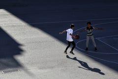 Δύο παιδιά παίζουν την καλαθοσφαίριση σε έναν αθλητικό τομέα οδών στοκ φωτογραφίες