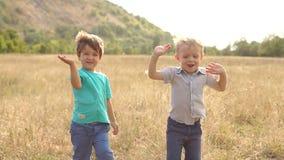 Δύο παιδιά που κυματίζουν τα χέρια τους στη κάμερα στο πάρκο απόθεμα βίντεο