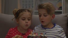 Δύο παιδιά που φυσούν τα κεριά στο κέικ γενεθλίων, φίλοι που χαμογελούν, εορτασμός φιλμ μικρού μήκους