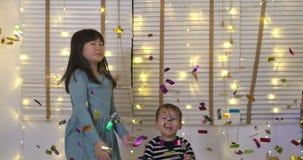 Δύο παιχνίδια παιδιών με το κομφετί και έχουν τη διασκέδαση που πηδά στο καθιστικό απόθεμα βίντεο