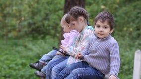 Δύο παιχνίδι μικρών κοριτσιών και αγοριών με το PC ταμπλετών στο θερινό πάρκο απόθεμα βίντεο