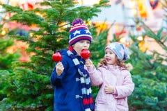 Δύο παιδάκια που τρώνε το μήλο ζάχαρης στην αγορά Χριστουγέννων Στοκ Φωτογραφίες