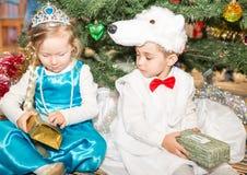 Δύο παιδιά έντυσαν στα κοστούμια καρναβαλιού κοντά στο δέντρο έλατου Χριστουγέννων σε νέο Year& x27 s children& x27 διακοπές του  Στοκ φωτογραφία με δικαίωμα ελεύθερης χρήσης