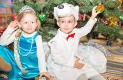 Δύο παιδιά έντυσαν στα κοστούμια καρναβαλιού κοντά στο δέντρο έλατου Χριστουγέννων σε νέο Year& x27 s children& x27 διακοπές του  Στοκ Εικόνα