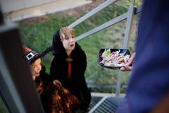 Δύο παιδιά, αγόρι και κορίτσι, στα σκοτεινά κοστούμια για αποκριές παίρνουν τις καραμέλες Στοκ Εικόνες