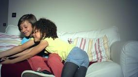 Δύο παιδιά αφροαμερικάνων στον καναπέ που υποστηρίζουν άνω της TV μακρινής απόθεμα βίντεο