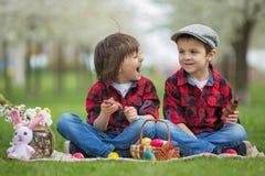 Δύο παιδιά, αδελφοί αγοριών, τρώγοντας τα λαγουδάκια σοκολάτας και έχοντας Στοκ Εικόνα