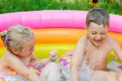 Δύο παιδιά που γελούν και που επιπλέουν ευτυχώς στη διογκώσιμη πισίνα στοκ εικόνα