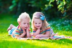 Δύο παιδιά που διαβάζουν στο θερινό κήπο Στοκ φωτογραφία με δικαίωμα ελεύθερης χρήσης