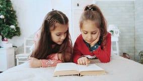 Δύο παιδιά που κάθονται σε ένα άσπρο δωμάτιο, που διαβάζει ένα βιβλίο στο πράσινο δέντρο υποβάθρου απόθεμα βίντεο