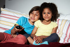 Δύο παιδιά που κάθονται στον καναπέ που προσέχει τη TV από κοινού στοκ εικόνες