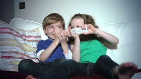 Δύο παιδιά που κάθονται στον καναπέ που υποστηρίζει άνω της TV μακρινής φιλμ μικρού μήκους