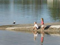 Δύο παιδιά που παίζουν κοντά στο νερό στην κεκλιμένη ράμπα βαρκών Στοκ φωτογραφία με δικαίωμα ελεύθερης χρήσης