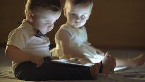 Δύο παιδιά που παίζουν με μια ταμπλέτα απόθεμα βίντεο