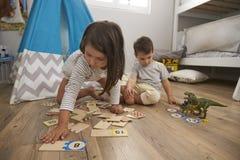 Δύο παιδιά που παίζουν το παιχνίδι γρίφων αριθμού μαζί στο χώρο για παιχνίδη Στοκ Φωτογραφίες