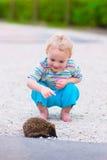 Δύο παιδιά που προσέχουν έναν σκαντζόχοιρο Στοκ Φωτογραφίες