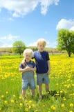 Δύο παιδιά που στέκονται έξω στο λιβάδι λουλουδιών Στοκ φωτογραφίες με δικαίωμα ελεύθερης χρήσης