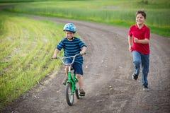 Δύο παιδιά που ταξιδεύουν μαζί με το ποδήλατό του στο αγροτικό τοπίο Στοκ φωτογραφία με δικαίωμα ελεύθερης χρήσης