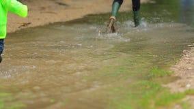 Δύο παιδιά που τρέχουν μέσω της μεγάλης λίμνης μετά από τη βροχή