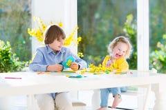 Δύο παιδιά που χρωματίζουν και που κόβουν τις ζωηρόχρωμες πεταλούδες εγγράφου Στοκ φωτογραφίες με δικαίωμα ελεύθερης χρήσης
