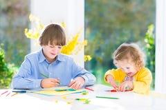 Δύο παιδιά που χρωματίζουν και που κόβουν τις ζωηρόχρωμες πεταλούδες εγγράφου Στοκ εικόνες με δικαίωμα ελεύθερης χρήσης