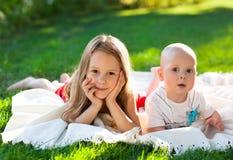 Δύο παιδιά στο πράσινο λιβάδι και το χαμόγελο Στοκ εικόνες με δικαίωμα ελεύθερης χρήσης