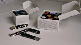 Δύο πακέτα με τα πολύχρωμα βάζα της χρωστικής ουσίας υφάσματος και οι μαύροι σωλήνες βρίσκονται σε μια άσπρη επιφάνεια απόθεμα βίντεο