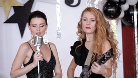 Δύο πανέμορφα κορίτσια στα μαύρα φορέματα που τραγουδούν στην κιθάρα σε ένα κόμμα φιλμ μικρού μήκους