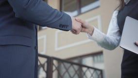 Δύο παραγνωρισμένοι συνέταιροι νεαρών άνδρων και γυναικών που τινάζουν τα χέρια στην κινηματογράφηση σε πρώτο πλάνο πεζουλιών Συν φιλμ μικρού μήκους