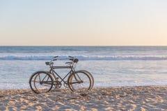 Δύο ποδήλατα στην παραλία ενάντια στα ωκεάνια κύματα στοκ εικόνα με δικαίωμα ελεύθερης χρήσης