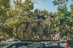 Δύο ποδήλατα τοποθετούνται στη συγκράτηση στεγών στη στέγη του αυτοκινήτου κάτω από τα πράσινα δέντρα στη σκιά Μεταφορά ποδηλάτων στοκ εικόνα με δικαίωμα ελεύθερης χρήσης