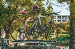 Δύο ποδήλατα τοποθετούνται στη συγκράτηση στεγών στη στέγη του αυτοκινήτου κάτω από τα πράσινα δέντρα στη σκιά Μεταφορά ποδηλάτων στοκ φωτογραφίες