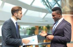 Δύο πολυεθνικοί νέοι επιχειρηματίες που συζητούν την επιχείρηση στη συνάντηση στην αρχή στοκ φωτογραφία