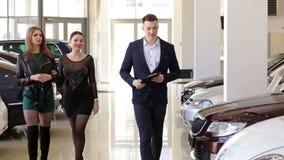 Δύο πολυτελή νέα κορίτσια σε μια συζήτηση εμποριών αυτοκινήτων σε έναν πωλητή αυτοκινήτων Πώληση αυτοκινήτων απόθεμα βίντεο